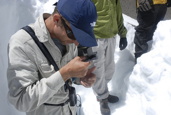 Examining snow crystals through a magnifying glass.